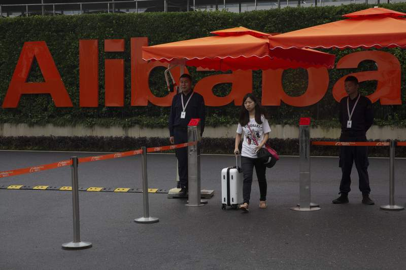 A woman pushing a trolley bag passes by security guards at the entrance to the Alibaba Group headquarters in Hangzhou, in eastern China's Zhejiang province on May 27, 2016. China's largest e-commerce company Alibaba said in a statement Sunday, Aug. 8, 2021, it is working with police to investigate alleged sexual misconduct at the company after a female employee reported that she had been sexually assaulted. (AP Photo/Ng Han Guan)
