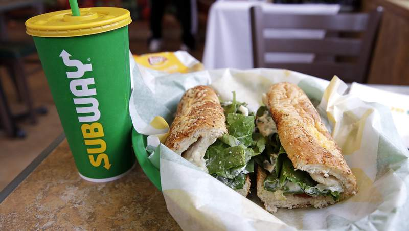 FILE - In this Friday, Feb. 23, 2018 file photo, the Subway logo is seen on a soft drink cup next to a sandwich at a restaurant in Londonderry, N.H.. Irelands Supreme Court has ruled that bread sold by the fast food chain Subway contains so much sugar that it cannot be legally defined as bread. (AP Photo/Charles Krupa, File)