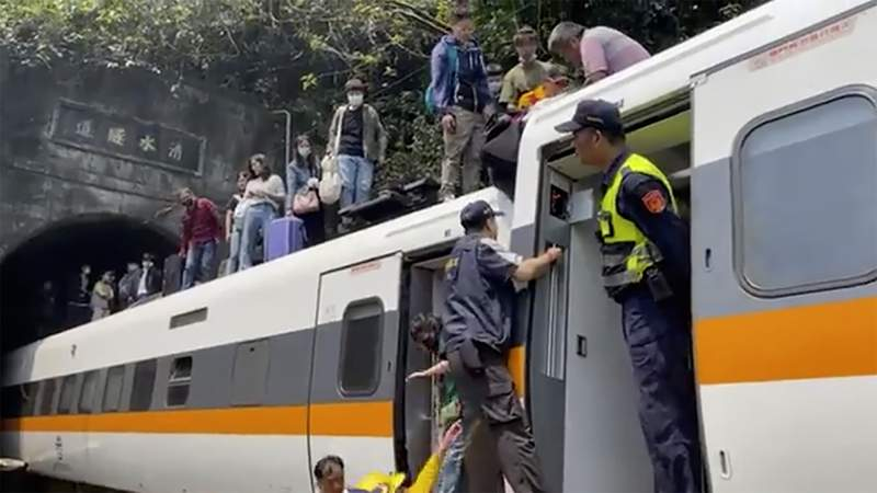 In this image made from a video released by hsnews.com.tw, passengers are helped to climb out of a derailed train in Hualien County in eastern Taiwan Friday, April 2, 2021. The train partially derailed along Taiwans east coast Friday, injuring an unknown number of passengers and causing potential fatalities. (hsnews.com.tw via AP)