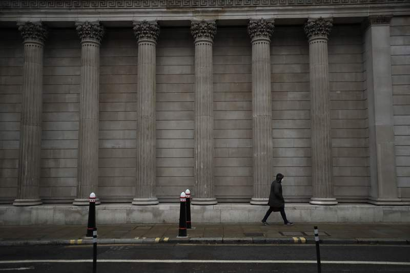 FILE - In this Jan. 5, 2021 file photo, a man wearing a face mask to curb the spread of coronavirus walks past part of the Bank of England in the City of London financial district, on the first morning of England entering a third national lockdown since the coronavirus outbreak began. The Bank of England on Tuesday July 13, 2021, ditched limits on dividends banks pay out to their shareholders that were first introduced at the outset of the coronavirus pandemic as part of a package of measures to shore up the British economy. (AP Photo/Matt Dunham, File)