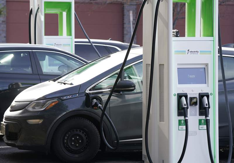 FILE - In this Dec. 21, 2020 file photo, a Chevrolet Bolt charges at an Electrify America site outside Colorado Mills outlet mall in downtown Lakewood, Colo. Electrify America, an electric vehicle charging network funded with money paid by Volkswagen as punishment for its emissions cheating scandal, says it plans to more than double its number of charging stations throughout the United States and Canada. The expansion will include 1,800 fast-charging stations and 10,000 individual chargers by 2025.  (AP Photo/David Zalubowski, File)