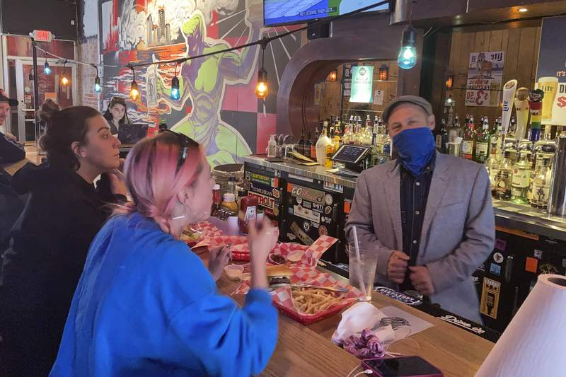In a photo from May 6, 2021, Timothy Tharp with patrons Cecelia Shelley, center, and Amber Nolan, at his Checker Bar in downtown Detroit. Tharp also owns Grand Trunk Pub and the Whisky Parlor. He estimates that his businesses have lost about $1 million after closures caused by the coronavirus pandemic. But now as vaccinations increase and government-ordered lockdowns and restrictions to protect the public are being lifted, Tharpe believes the coronavirus pandemic could be remembered as just another hurdle the Motor City has had to leap. (AP Photo/Corey Williams)