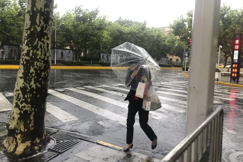 Una mujer con un paraguas se protege del viento y la lluvia al paso del tifn In-fa por Shanghi, en China, el domingo 25 de julio de 2021. (AP Foto/Chen Si)