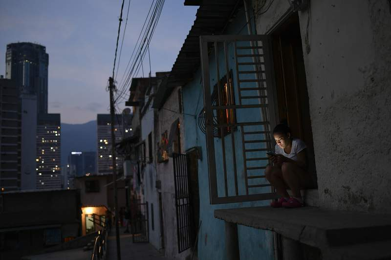 A woman looks at her smart phone outside of her home in the San Agustin neighborhood of Caracas, Venezuela, Sunday, May 17, 2020. President Nicolas Maduro is relaxing quarantine measures over the weekend by allowing children and older adults out of their homes for a few hours each day. (AP Photo/Matias Delacroix)