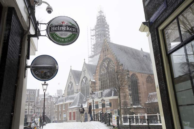 A Heineken sign sits on the facade of a bar, closed because of the coronavirus lockdown in Amsterdam, Sunday, Feb. 7, 2021. Dutch beer brewer Heineken said Wednesday it plans to cut 8,000 staff, nearly 10% of its global workforce, as part of a cost-cutting reorganization after a pandemic-dominated year that saw it sink to a net loss of 204 million euros ($248 million). (AP Photo/Peter Dejong)