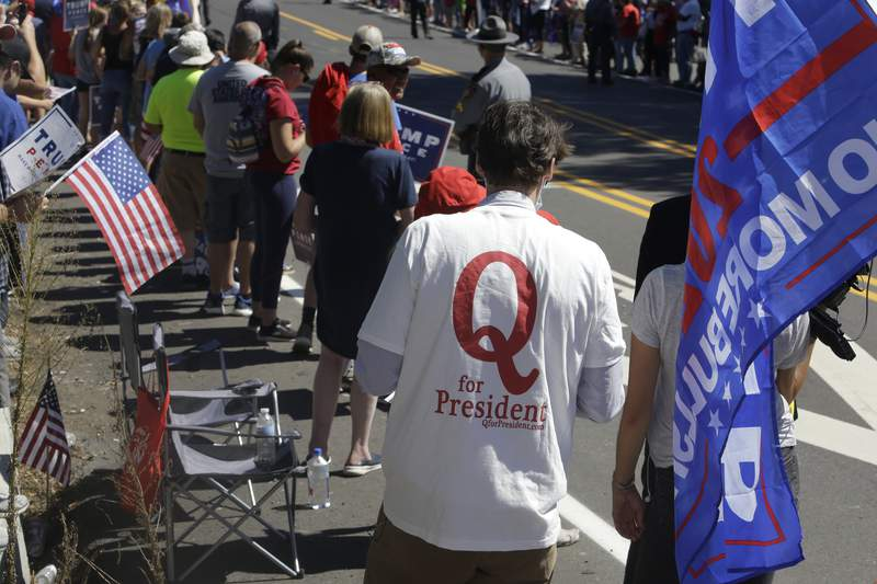 FILE - In this Aug. 20, 2020, file photo, a man in a QAnon T-shirt walks among Trump supporters as they wait for President Donald Trump to arrive and visit Mariotti Building Products in Old Forge, Pa.Experts and former QAnon believers say they have tips for anyone wondering how to talk to people consumed by the conspiracy theory. (AP Photo/Jacqueline Larma, File)