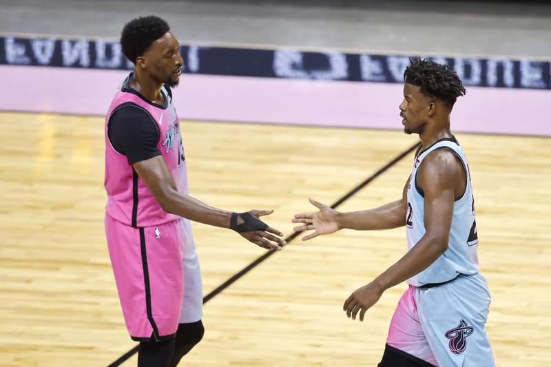 Jimmy Butler of the Miami Heat high fives Bam Adebayo against the Philadelphia 76ers during the first quarter at American Airlines Arena on May 13, 2021 in Miami, Florida.