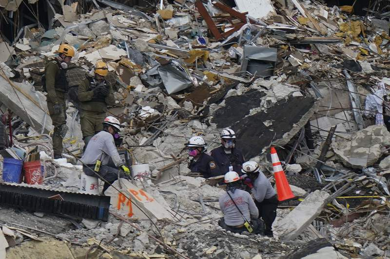Members of an Israel team, top left, work alongside local search and rescue personnel atop the rubble at the Champlain Towers South condo building, where scores of people remain missing almost a week after it partially collapsed, Wednesday, June 30, 2021, in Surfside, Fla. (AP Photo/Lynne Sladky)