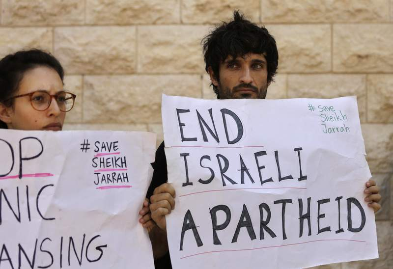 Protesters hold signs during a hearing on the possible evictions of Palestinian from the Sheikh Jarrah neighborhood of Jerusalem, outside the Supreme Court in Jerusalem, Monday, Aug. 2, 2021. (AP Photo/Maya Alleruzzo)