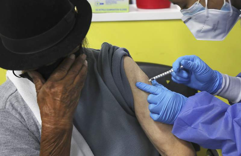An elderly woman covers her face as she is inoculated with a dose of the Pfizer COVID-19 vaccine at the convention center converted into a vaccination site, in Quito, Ecuador, Wednesday, March 31, 2021.  (AP Photo/Dolores Ochoa)