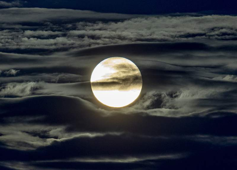 FILE - In this Sept. 2, 2020 file photo, the full moon shines surrounded by clouds in the outskirts of Frankfurt, Germany.  Future moon explorers will face ultrahazardous radiation levels. That's the conclusion of a new study published by Chinese and German scientists Friday, Sept. 25. The researchers say astronauts on the moon will be bombarded with two to three times more radiation than astronauts currently circling Earth aboard the International Space Station.(AP Photo/Michael Probst, File)