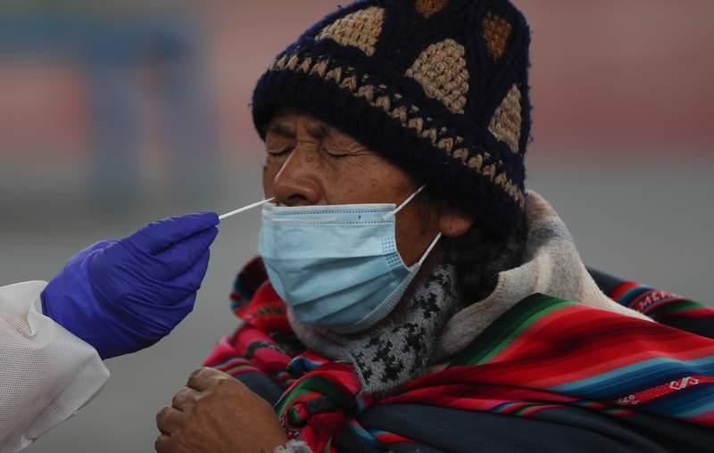 Un trabajador de salud toma una muestra de un residente para detectar contagios del nuevo coronavirus en una instalacin deportiva en La Paz, Bolivia, el viernes 8 de enero de 2021. (AP Foto/Juan Karita)