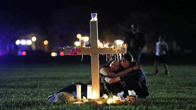 Two people comfort each other as they sit and mourn at one of 17 crosses after a candlelight vigil for the victims of the shooting at Marjory Stoneman Douglas High School in February 2018.