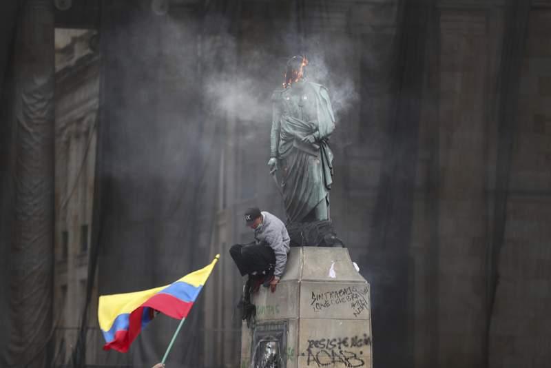 Un manifestante baja de una estatua del hroe independentista Simn Bolvar despus de prender fuego a una malla protectora en su cabeza, durante una marcha contra el gobierno en la Plaza Bolvar en Bogot, Colombia, el mircoles 12 de mayo de 2021. (AP Foto/Fernando Vergara)
