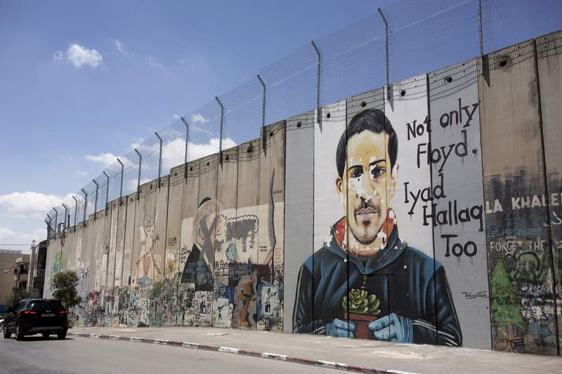 A mural depicting Eyad Hallaq, an autistic Palestinian man who was killed by Israeli police in Jerusalem's Old City last year, is seen on Israel's controversial separation barrier, in the West Bank town of Bethlehem, Friday, April 9, 2021. Israeli prosecutors on Thursday, June 17, 2021 charged a border police officer with reckless manslaughter in the deadly shooting. (AP Photo / Maya Alleruzzo)