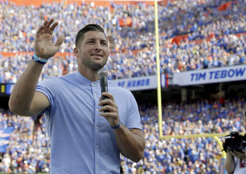 FILE - Former Florida football player Tim Tebow speaks to fans after he was inducted in the Ring of Honor at Florida Field during the first half of an NCAA college football game against LSU in Gainesville, Fla., in this Saturday, Oct. 6, 2018, file photo. Tebow and Urban Meyer are apparently getting back together, this time in the NFL. The former Florida star and 2007 Heisman Trophy-winning quarterback is expected to team up with his college coach by signing a one-year contract to play for the Jacksonville Jaguars, the NFL Network reported Monday, May 10, 2021. (AP Photo/John Raoux, File)