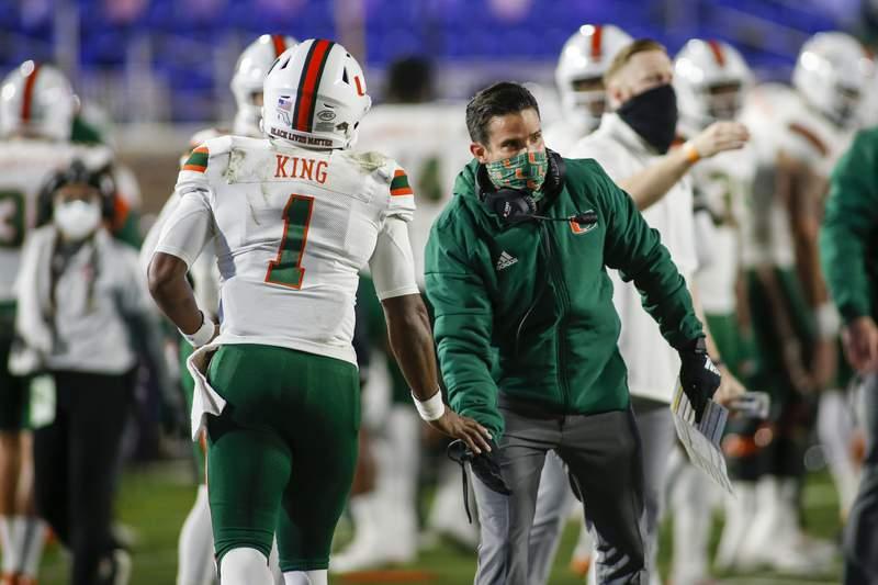 Miami coach Manny Diaz congratulates quarterback D'Eriq King (1) after a touchdown pass against Duke during the first quarter of an NCAA college football game Saturday, Dec. 5, 2020, in Durham, N.C. (Nell Redmond/Pool Photo via AP)