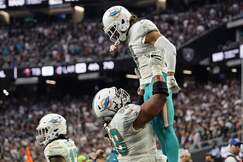 Dolphins guard Robert Hunt holds up wide receiver Will Fuller after Fuller scored a two-point conversion against the Las Vegas Raiders during the second half Sunday, Sept. 26, 2021, in Las Vegas.