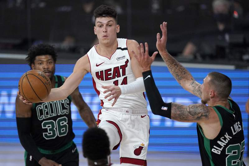 Miami's Tyler Herro goes up to make a pass between Boston's Marcus Smart and Daniel Theis during the first half of Game 1 on Tuesday.