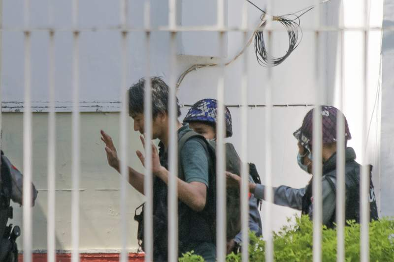 In this Feb. 26, 2021, photo, Japanese journalist Yuki Kitazumi raises his hands as he is escorted by police upon arrival at the Myaynigone police station in Sanchaung township in Yangon, Myanmar.  Japan's government said Monday, April 19, 2021 it is asking Myanmar to release the Japanese journalist who was arrested by security forces in its largest city of Yangon the previous day. (AP Photo)