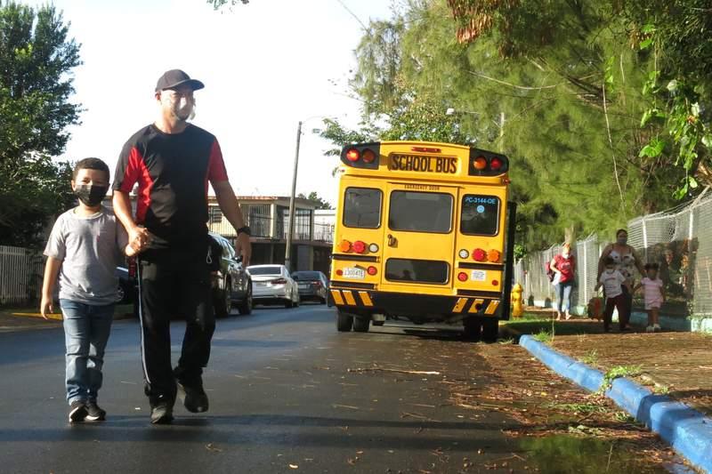 Estudiantes llegan a la escuela primaria Ramn Marn Sol, en San Juan, Puerto Rico, por primera vez en casi un ao en medio de la pandemia de coronavirus, el mircoles, 10 de marzo del 2021. La isla est reabriendo algunas escuelas pblicas.  (AP Foto/Dnica Coto)