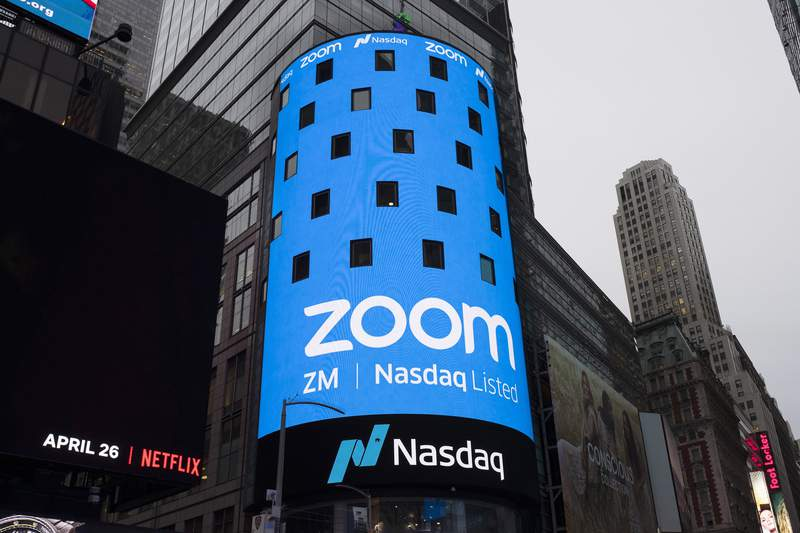 FILE - This April 18, 2019, file photo shows a sign for Zoom Video Communications ahead of the company's Nasdaq IPO in New York. Federal regulators are requiring Zoom to strengthen its security in a proposed settlement of allegations that the video conferencing service misled users about its level of security for meetings. The settlement was announced Monday, Nov. 9, 2020, by the Federal Trade Commission.  (AP Photo/Mark Lennihan, File)
