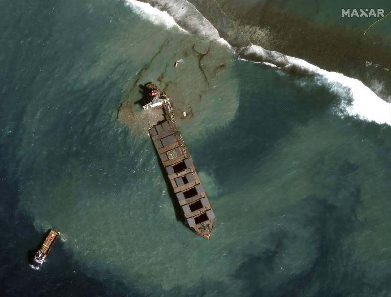 This satellite image provided by 2020 Maxar Technologies on Tuesday Aug. 18, 2020, showing an aerial view of the MV Wakashio, a bulk carrier ship that recently ran aground off the southeast coast of Mauritius. Officials say the grounded Japanese ship that leaked tons of oil near protected areas off the Indian Ocean island nation of Mauritius, has split apart with remaining fuel seen spreading into the turquoise waters. (2020 Maxar Technologies via AP)