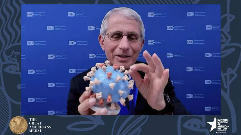 This image from video provided by Smithsonian's National Museum of American History shows Dr. Anthony Fauci, director of the National Institute of Allergy and Infectious Diseases and chief medical adviser to the president, holding his personal 3D model of the COVID-19 virus he is donating to the Smithsonians National Museum of American History on Tuesday, March 2, 2020. Fauci presented the donation Tuesday night in a virtual ceremony to honor him with the museums Great Americans Medal.  (Smithsonian's National Museum of American History via AP)