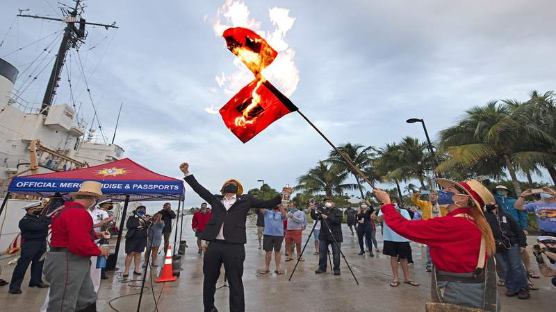 In this photo provided by the Florida Keys News Bureau, Jai Sommers holds hurricane flags as they burn after being doused with rum to mark the end of the 2020 Atlantic hurricane season, Monday, Nov. 30, 2020, in Key West, Fla. According to the National Oceanographic and Atmospheric Administration, the 2020 season spawned 30 named storms including 13 hurricanes, making it the busiest on record. The flag-burning ceremony capped the Florida Keys' Conch Republic Independence Celebration, honoring the Florida Keys island chain's colorful alter ego.