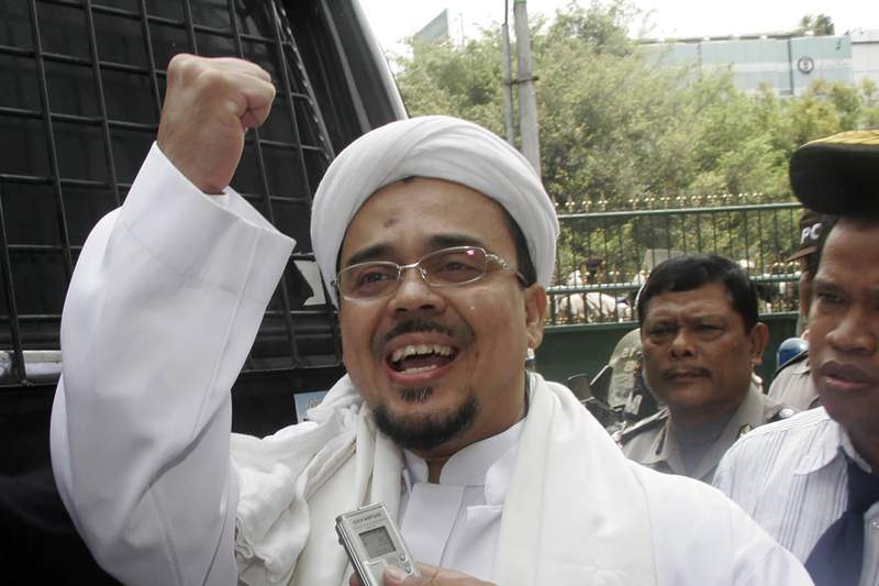 """FILE - In this Oct. 30, 2008, file photo, Rizieq Shihab, leader of the Islamic Defenders Front (FPI), shouts """"Allahu Akbar!"""" (God is great) after his trial at central Jakarta district court, Indonesia. Thousands of followers of the firebrand cleric joyfully welcomed him at an Indonesian airport early Tuesday, Nov. 10, 2020 as he returned home from a 3-year exile in Saudi Arabia after criminal charges including a pornography case were dropped. (AP Photo, File)"""
