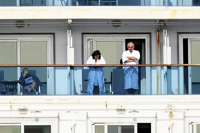 Passengers look out from balconies aboard the Grand Princess as it cruises a holding pattern about 25 miles off the coast of San Francisco on Sunday, March 8, 2020. The ship is expected to dock in Oakland in the east San Francisco Bay on Monday. California Gov. Gavin Newsom and the mayor of Oakland sought Sunday to reassure the public that none of the passengers from the ship with multiple cases of the new coronavirus will be released into the public before undergoing a 14-day quarantine. (AP Photo/Noah Berger)