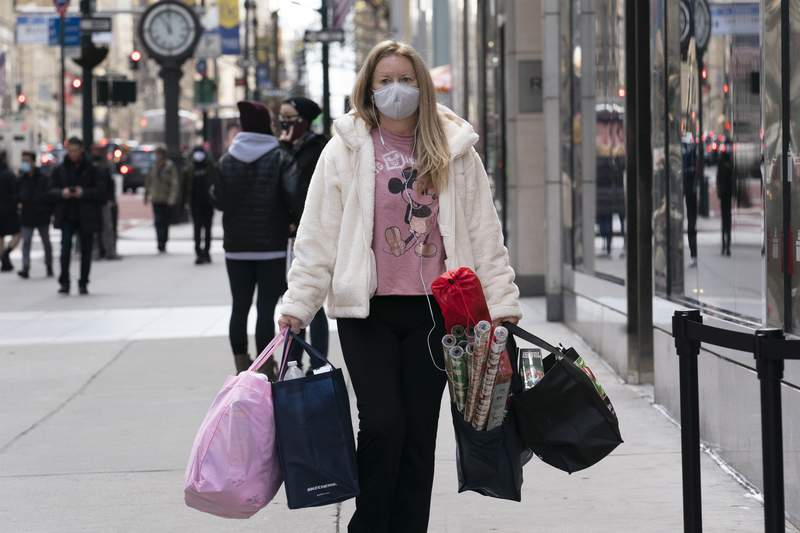 FILE - A woman carries shopping bags, Thursday, Dec. 10, 2020, in New York.  U.S. consumer spending fell 0.4% in November, the first decline since April, as Americans confronted a newly resurgent virus. The Commerce Department reported Wednesday, Dec. 23,  that the November decline followed a 0.3% gain in October and even bigger increases starting in May as the country emerged from a pandemic lockdown that had been imposed to try to stop the spread of the virus.  (AP Photo/Mark Lennihan)