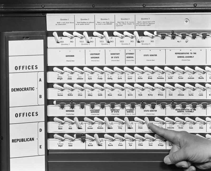 "The original caption on this undated photo says, ""After you have completed casting your ballot, move the large curtain handle to the left. This will record your vote, wipe off the 'X' marks and return all the voting levers to an upright position, before opening the curtain."""