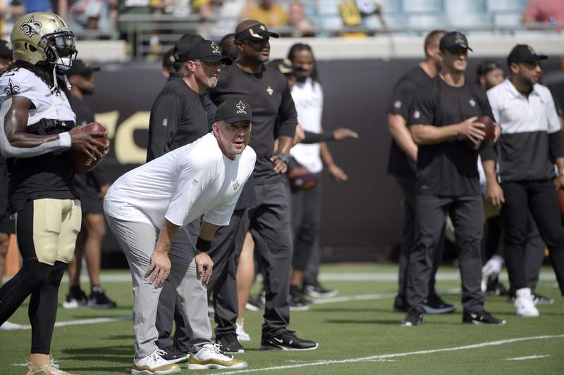 FILE - In this Sunday, Sept. 12, 2021, file photo, New Orleans Saints head coach Sean Payton, second from left, watches players warm up before an NFL football game against the Green Bay Packers in Jacksonville, Fla. Six unidentified members of the Saints coaching staff, a player and a nutritionist have tested positive for COVID-19, two people familiar with the situation said, Tuesday, Sept. 14, 2021. The people spoke with The Associated Press on Tuesday on condition of anonymity because the team and NFL had not made a public statement about the matter. The names of those who tested positive were not expected to be released in the short term because of federal medical privacy laws. (AP Photo/Phelan M. Ebenhack, File)