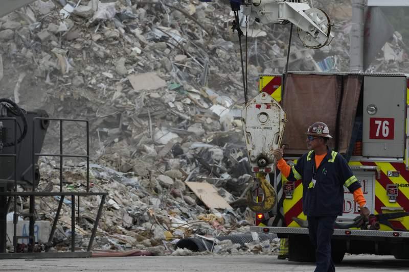 Operarios trabajan entre los escombros de la parte demolida del edificio Champlain Towers South, mientras continan las labores de bsqueda en la seccin del inmueble del departamento que se vino abajo, el 12 de julio de 2021, en Surfside, Florida. (AP Foto/Rebecca Blackwell)