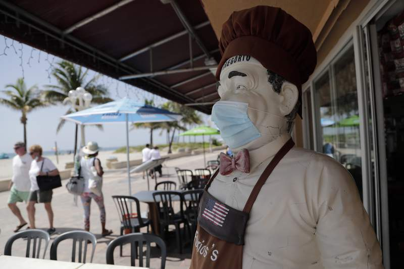 A statue of a chef wears a protective face mask on the Hollywood Beach Broadwalk in this file photo.