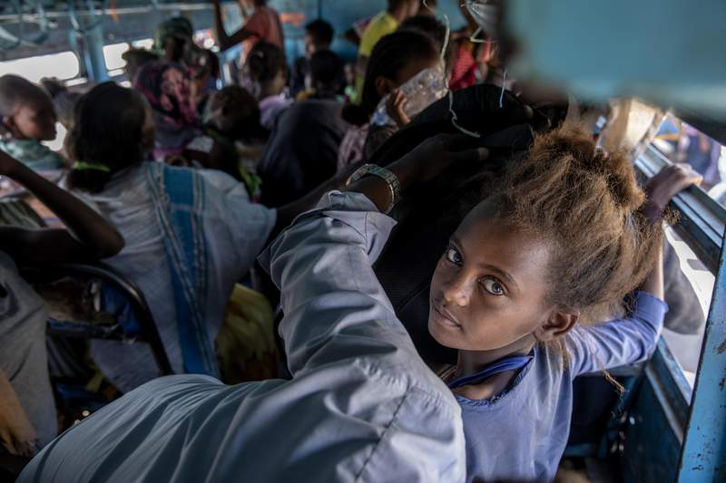 FILE - In this Dec. 1, 2020, file photo, refugees who fled the conflict in the Ethiopia's Tigray ride a bus going to the Village 8 temporary shelter, near the Sudan-Ethiopia border, in Hamdayet, eastern Sudan. In a remote part of neighboring Sudan, no coronavirus testing is taking place in the crowded camps that are now home to more than 45,000 Ethiopian refugees. People share shelters and stand close together in lines for food, cash and registration. There are few face masks to be seen. (AP Photo/Nariman El-Mofty, File)
