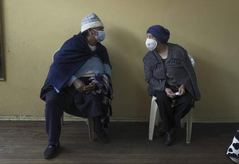 Women visit with eachother as they wait for a shot of the COVID-19 vaccine in Pillaro, Ecuador, Thursday, July 8, 2021. (AP Photo/Dolores Ochoa)