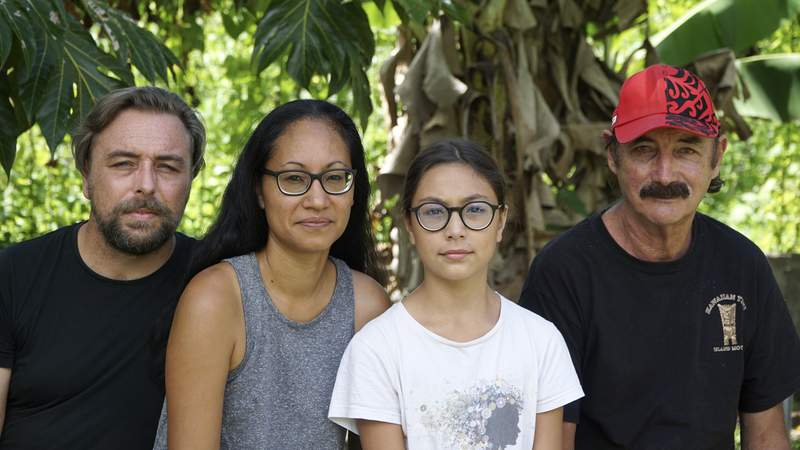 A group who have been stranded in Tahiti, pictured from left, Benjamin Baude, Kissy Ika Chavez Baude, Gaa Baude Ika and Thierry Gourtay in Afareaitu on Moorea Island, Tahiti, Saturday, Sept. 19, 2020. A group of 25 residents from remote Easter Island has been stranded far from home for six months now. Many arrived in March planning to stay for just a few weeks. But they got stuck when the virus swept across the globe and their flights back home on LATAM airlines were canceled. LATAM says it doesn't know when it will restart the route.(Teraihau Rio via AP)