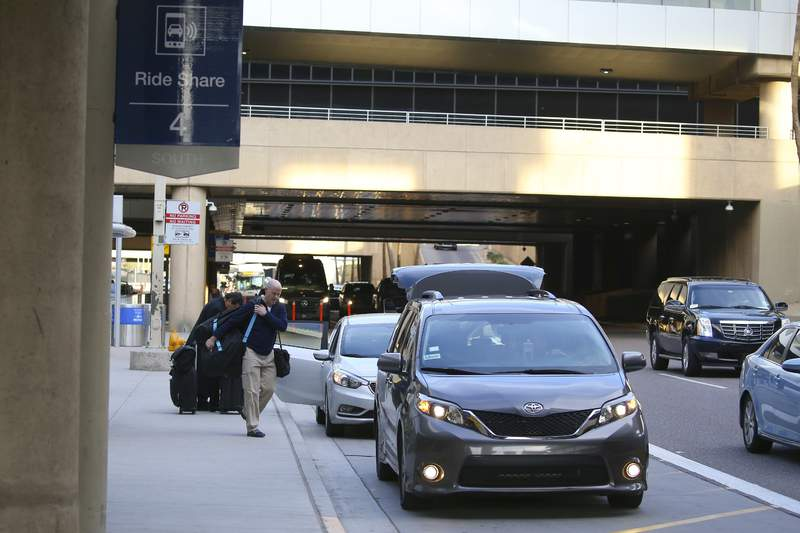 """FILE - In this Dec. 18, 2019, file photo passengers find their rides at the Ride Share point as they exit Phoenix Sky Harbor International Airport in Phoenix. A new $4 fee on Uber and Lyft rides to and from the Phoenix airport is """"very likely"""" unconstitutional, the state attorney general said Thursday, Jan. 16, 2020, upping the ante in the showdown that has led the ride-hailing giants to threaten to abandon the airport service. (AP Photo/Ross D. Franklin, File)"""