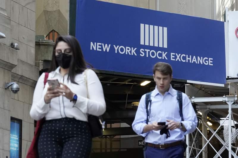 Dos personas caminan el mircoles 16 de junio de 2021 frente a la Bolsa de Valores de Nueva York. (AP Foto/Richard Drew)