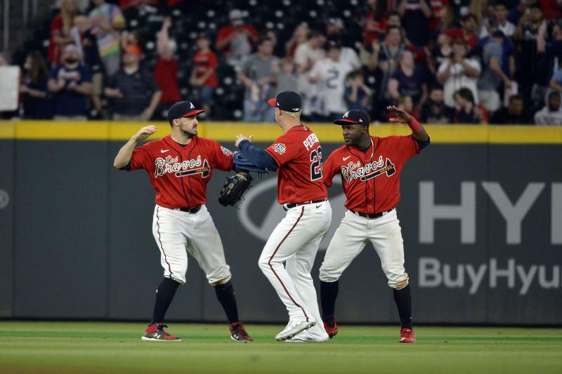 Adam Duvall, Joc Pedersen, and Guillermo Heredia of the Atlanta Braves celebrate after their win against the Miami Marlins at Truist Park on September 10, 2021 in Atlanta, Georgia.