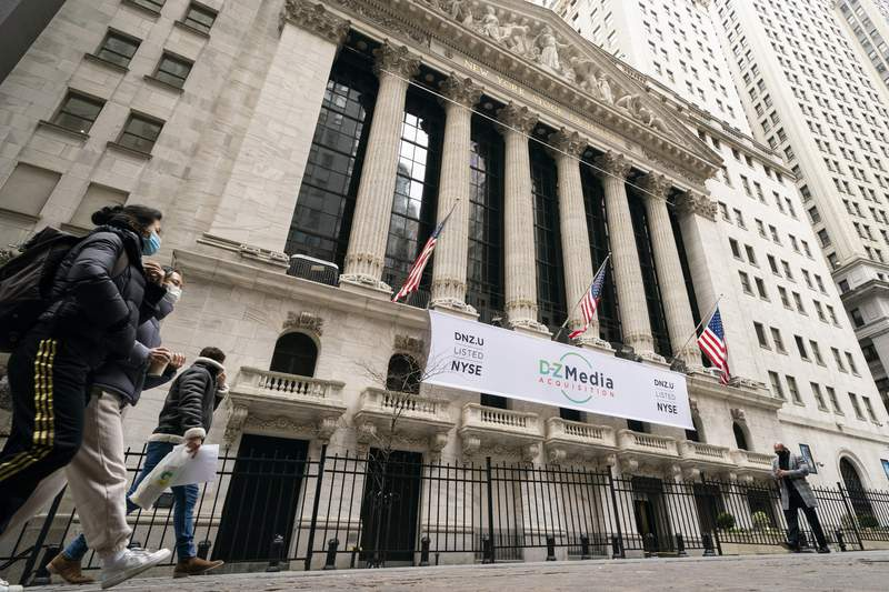 FILE - Pedestrians pass the New York Stock Exchange, Wednesday, Jan. 27, 2021, in New York. Stocks are opening higher on Wall Street, keeping the S&P 500 on track for its fourth weekly gain in a row. The benchmark index was up 0.3% in the early going Friday, April 16, led by gains in banks, industrial and health care companies.  (AP Photo/John Minchillo, File)