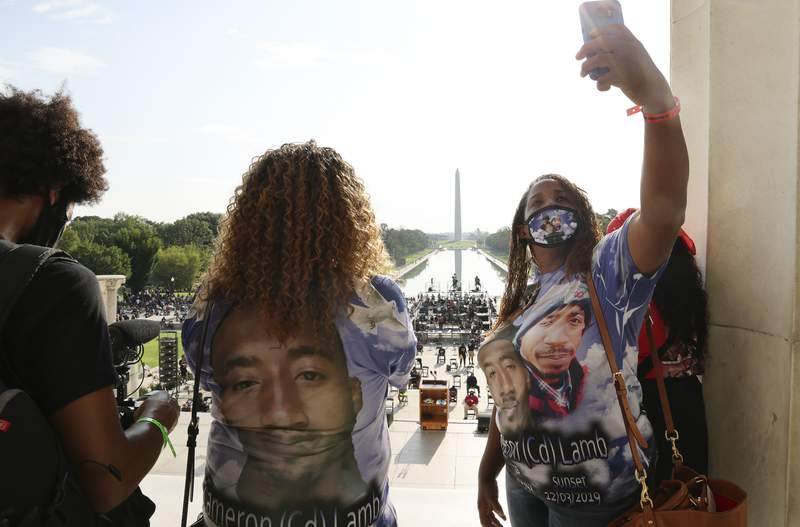 FILE - In this Aug. 28, 2020 file photo, Laurie Bey, right, whose son Cameron Lamb was shot and killed by Kansas City police in 2019, stands with Merlon Ragland, Cameron's aunt, as demonstrators gather at the Lincoln Memorial as final preparations are made for the March on Washington in Washington. The family of Lamb is suing Kansas City police and the officer. The Kansas City Star reports that the lawsuit was filed Monday, June 28, 2021, in federal court on behalf of 26-year-old Cameron Lamb's four minor children.(Jonathan Ernst/Pool via AP File)