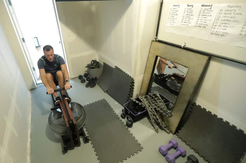 Neal Browning, the second person to receive a trial dose of a COVID-19 vaccine, works out on a home rowing machine, Friday, July 24, 2020, in Bothell, Wash. As the world's biggest COVID-19 vaccine study gets underway more than four months after Browning and 44 others became the first participants in a phase-one coronavirus vaccine study that has produced encouraging results, more than 150,000 Americans have filled out an online registry in recent weeks signaling interest to volunteer for other studies, according to a virologist with the Fred Hutchinson Cancer Research Institute in Seattle. (AP Photo/Ted S. Warren)