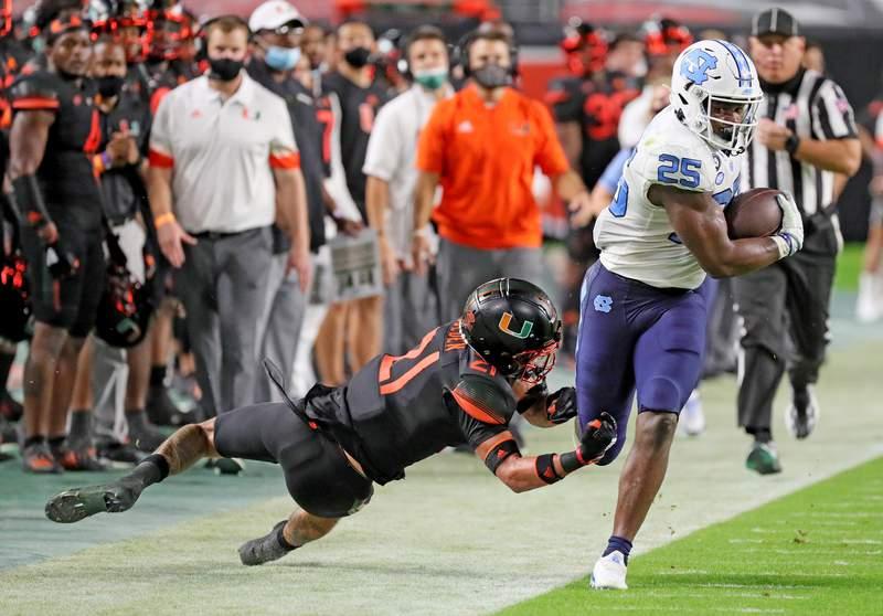 Miami Hurricanes safety Bubba Bolden (21) can't hold onto North Carolina Tar Heels running back Javonte Williams (25) in the third quarter at Hard Rock Stadium In Miami Gardens, Florida, Saturday, December 12, 2020.
