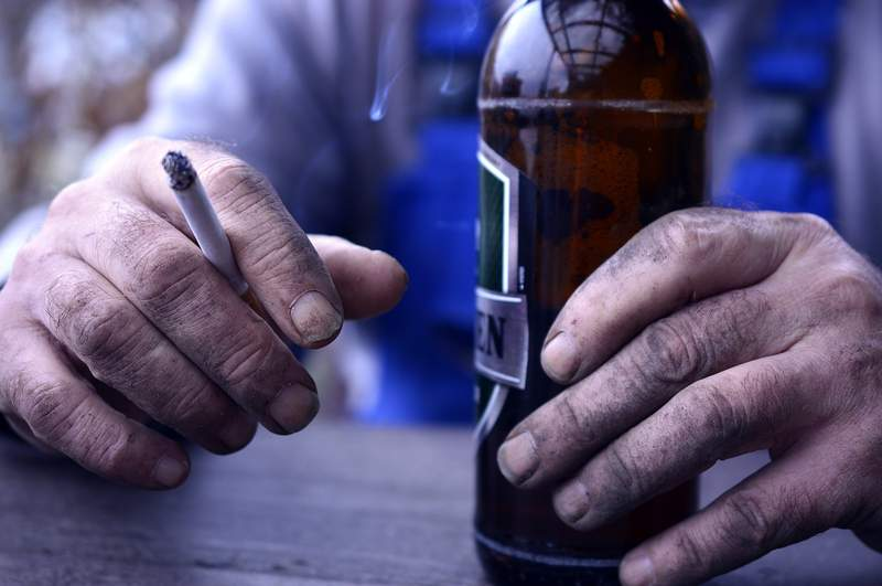 A man drinks a beer and smokes a cigarette.