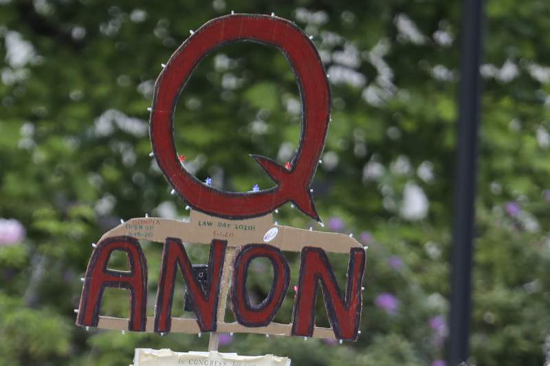 FILE - In this May 14, 2020, file photo, a person carries a sign supporting QAnon during a protest rally in Olympia, Wash, USA.  The social media company Twitter said Tuesday Jan. 12, 2021, it has suspended more than 70,000 accounts associated with the far right QAnon conspiracy theory following last week's U.S. Capitol insurrection. (AP Photo/Ted S. Warren, File)