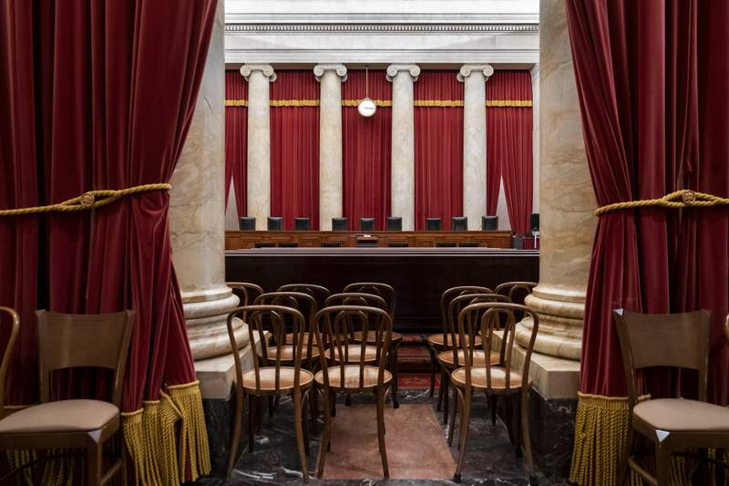FILE - In this June 24, 2019 file photo, the empty courtroom is seen at the U.S. Supreme Court in Washington.  Because of the coronavirus pandemic the Supreme Court is holding arguments by phone for the first time in its 230-year history. Attorneys say the teleconference arguments in 10 cases over six days present a range of challenges.  (AP Photo/J. Scott Applewhite, File)