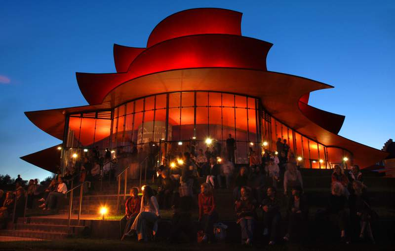 FILE - In this Sept.22, 2006 file photo people sit in front of the illuminated Potsdam's new Hans Otto theater after the opening ceremony. The new building was designed by Pritzker Architecture price awarded German architect Gottfried Boehm. Boehm died Wednesday, aged 101. (AP Photo/Sven Kaestner, file)